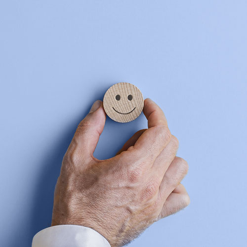 Illustration of a hand placing a wooden smiley