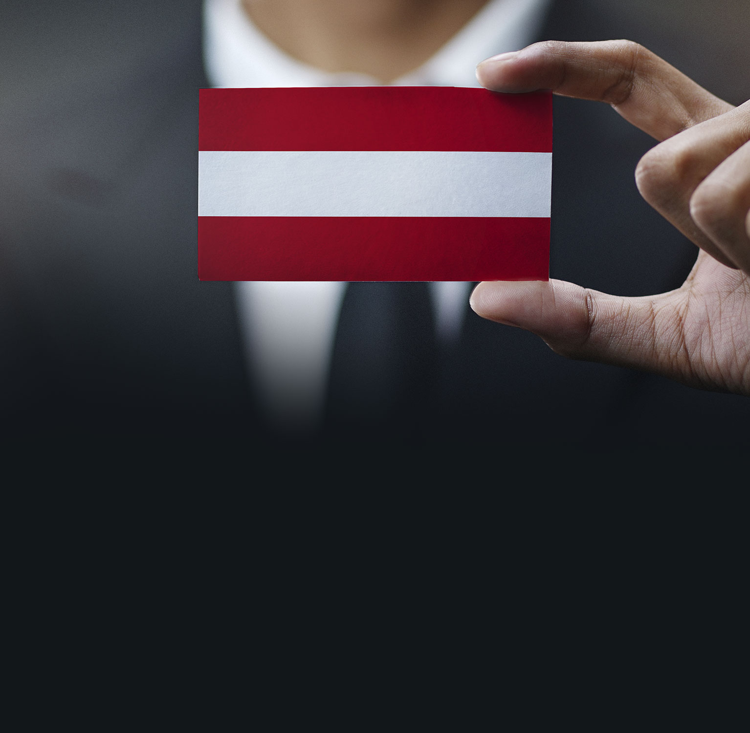Business professional holding up an Austrian flag themed card