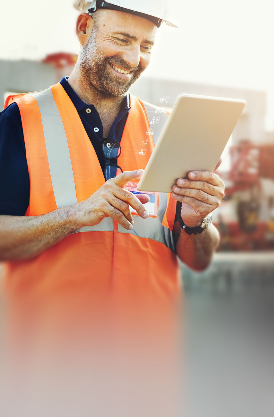 Man on construction site checking tablet to see delivery status